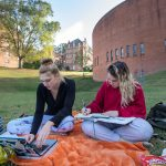 Students study on the lawn next to the Houston Memorial Chapel
