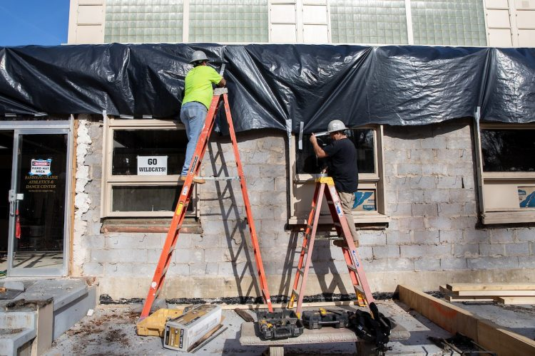 Construction workers make improvements to the exterior of the athletics center