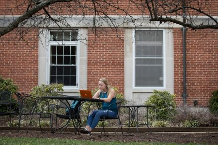 Student studies alone on a patio with a laptop.