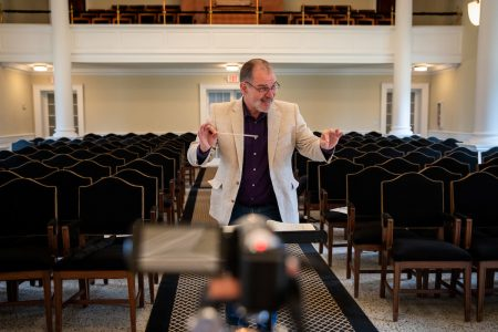 Music professor Randall Speer recorded himself conducting with an accompanist to send to chorale and orchestra students, so they could record themselves performing along to the same master track. The video was shot from multiple angles to give each group a unique view.