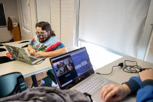 Mitchell Doss '21 and other in-person students connect with their virtual classmates during one of Warren's classes.