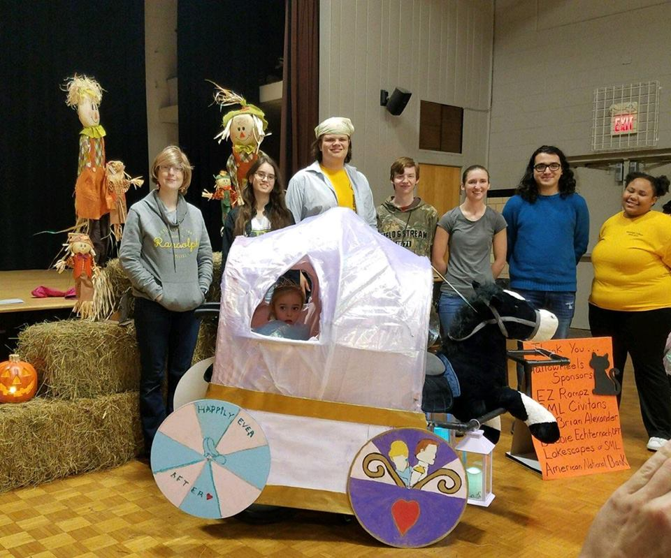 """Randolph students pose with Maddie, age 6, in her Cinderella-themed costume, """"Maddierella"""""""