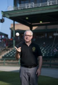 President Bradley W. Bateman looks determined as he tosses a baseball in the air preparing to throw out the first pitch